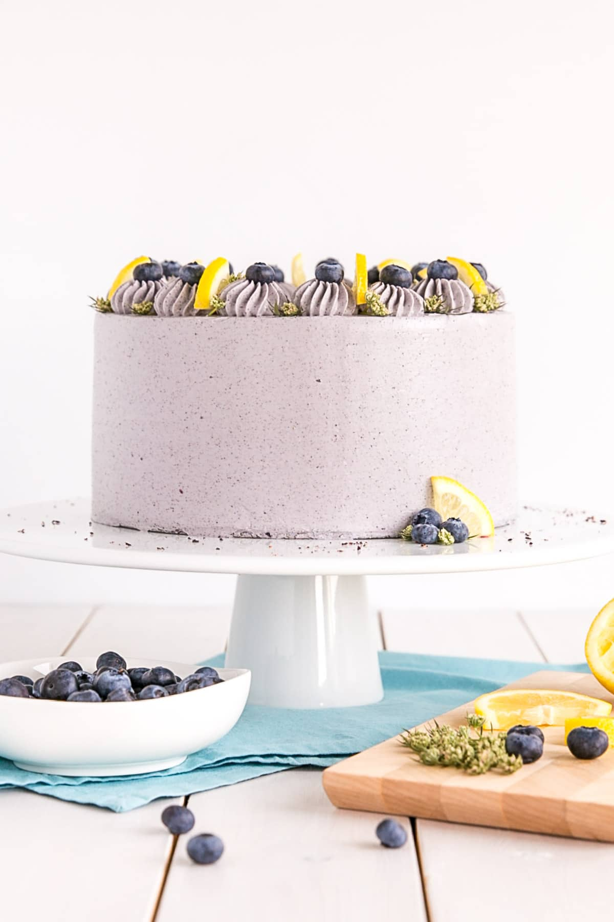 Cake on a white cake stand with a blue cloth underneath and a bowl of blueberries on the side.