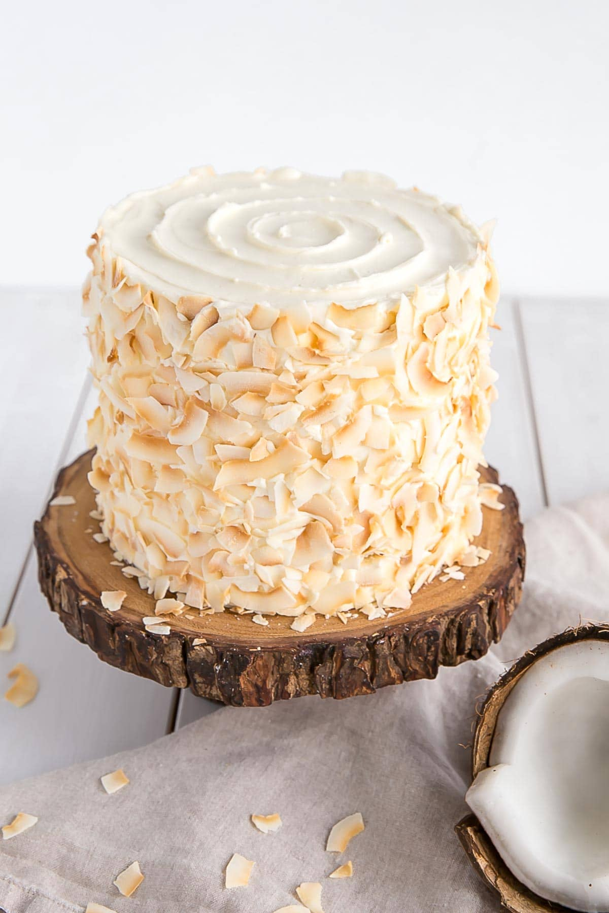 Homemade coconut cake decorated with toasted coconut and a swirl of frosting on the top.