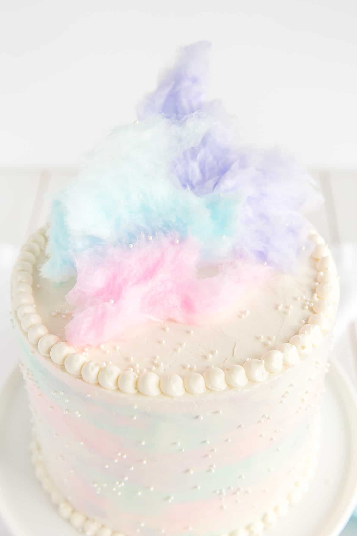 The top of this Cotton Candy Cake decorated with cotton candy and white sprinkles.