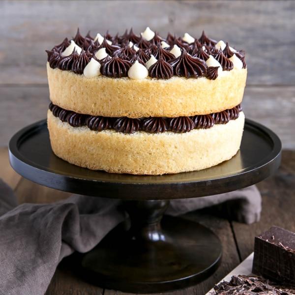 The classic Boston Cream Pie gets a modern makeover! Vanilla cake layers, creamy custard, and a rich chocolate ganache. | livforcake.com