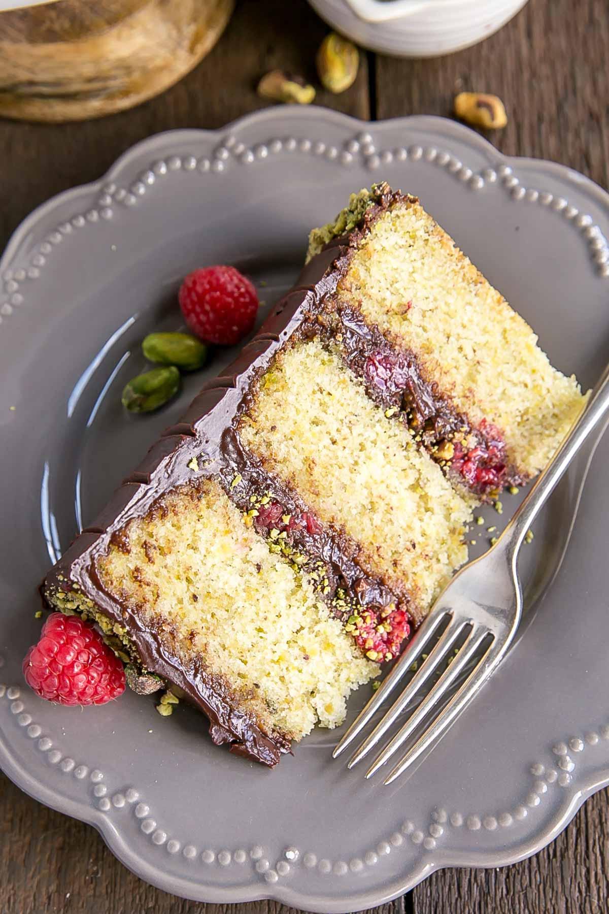 Cut slice of Pistachio Cake with Dark Chocolate Ganache and fresh Raspberries.