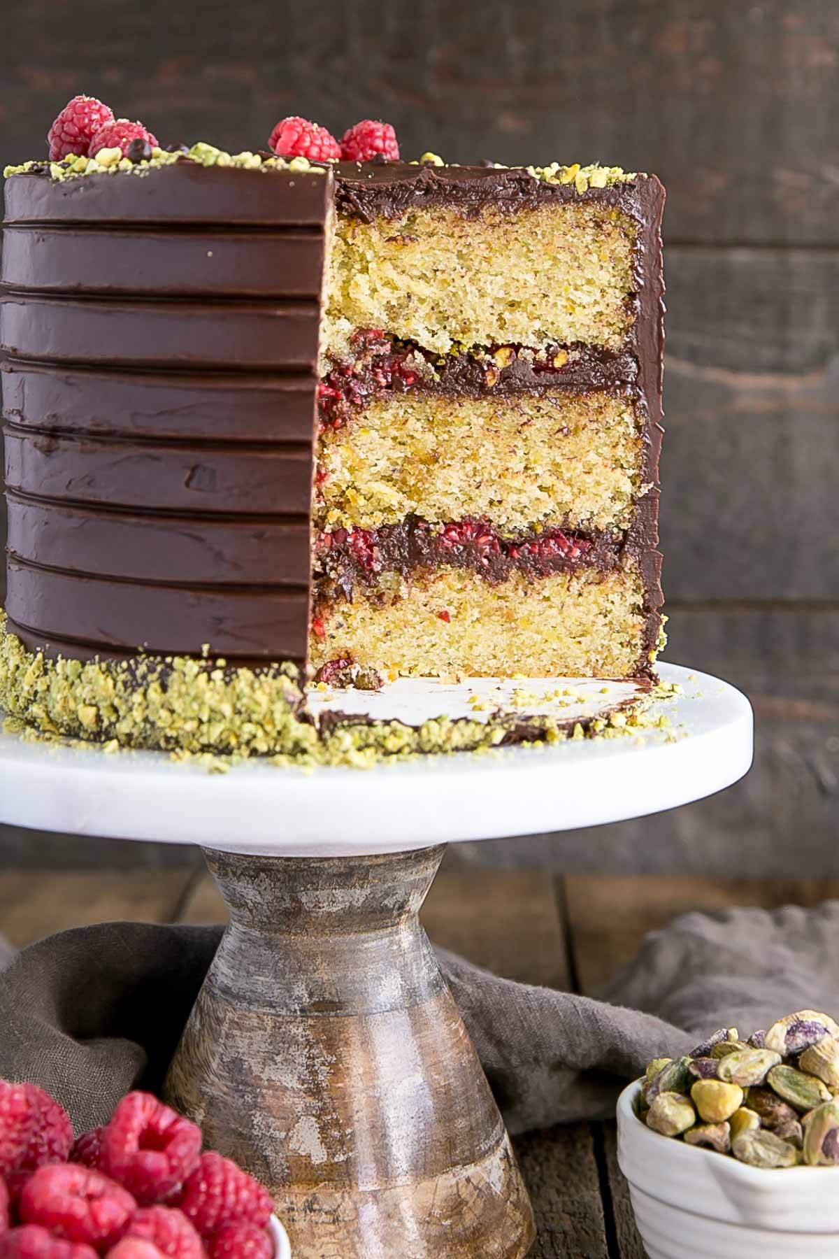 Pistachio cake layers with dark chocolate ganache and fresh raspberries.
