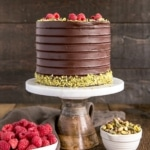 This Pistachio Cake recipe has loads of freshly ground pistachios in the cake batter and is layered with a rich dark chocolate ganache and fresh raspberries. | livforcake.com