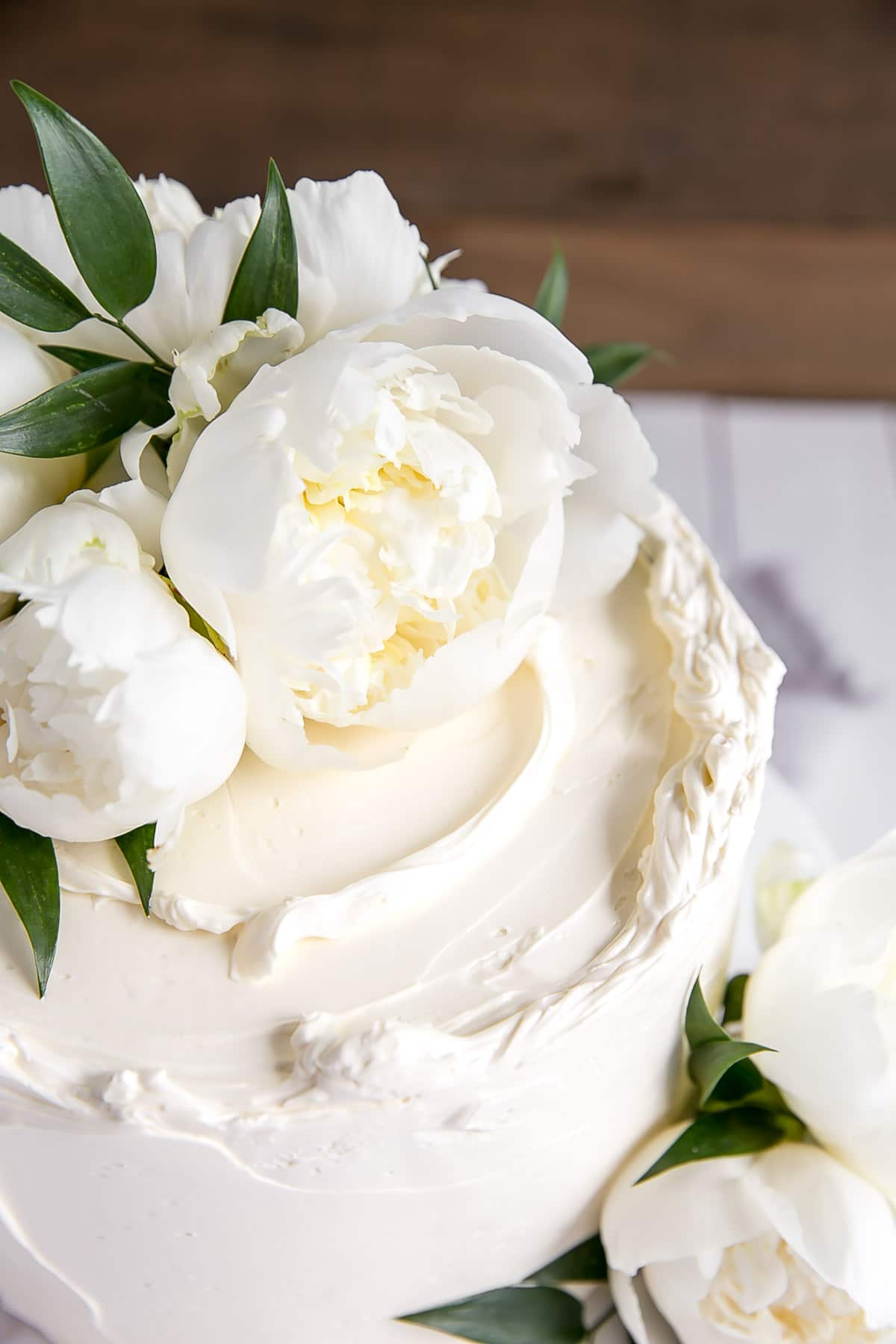 Close up of a Lemon Elderflower Cake with peonies
