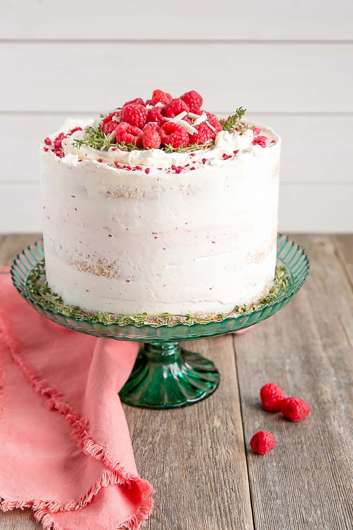 Rustic white chocolate raspberry cake with thyme sprigs.