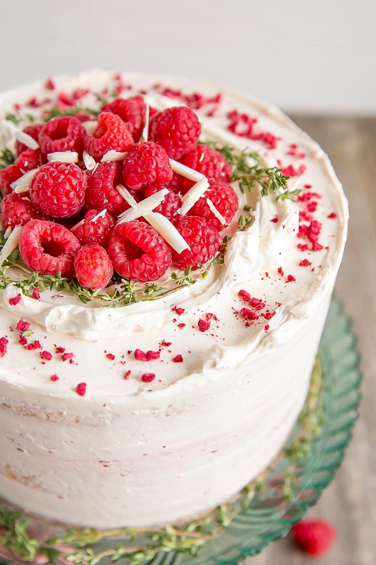 Close up of fresh raspberries on top of a white chocolate cake