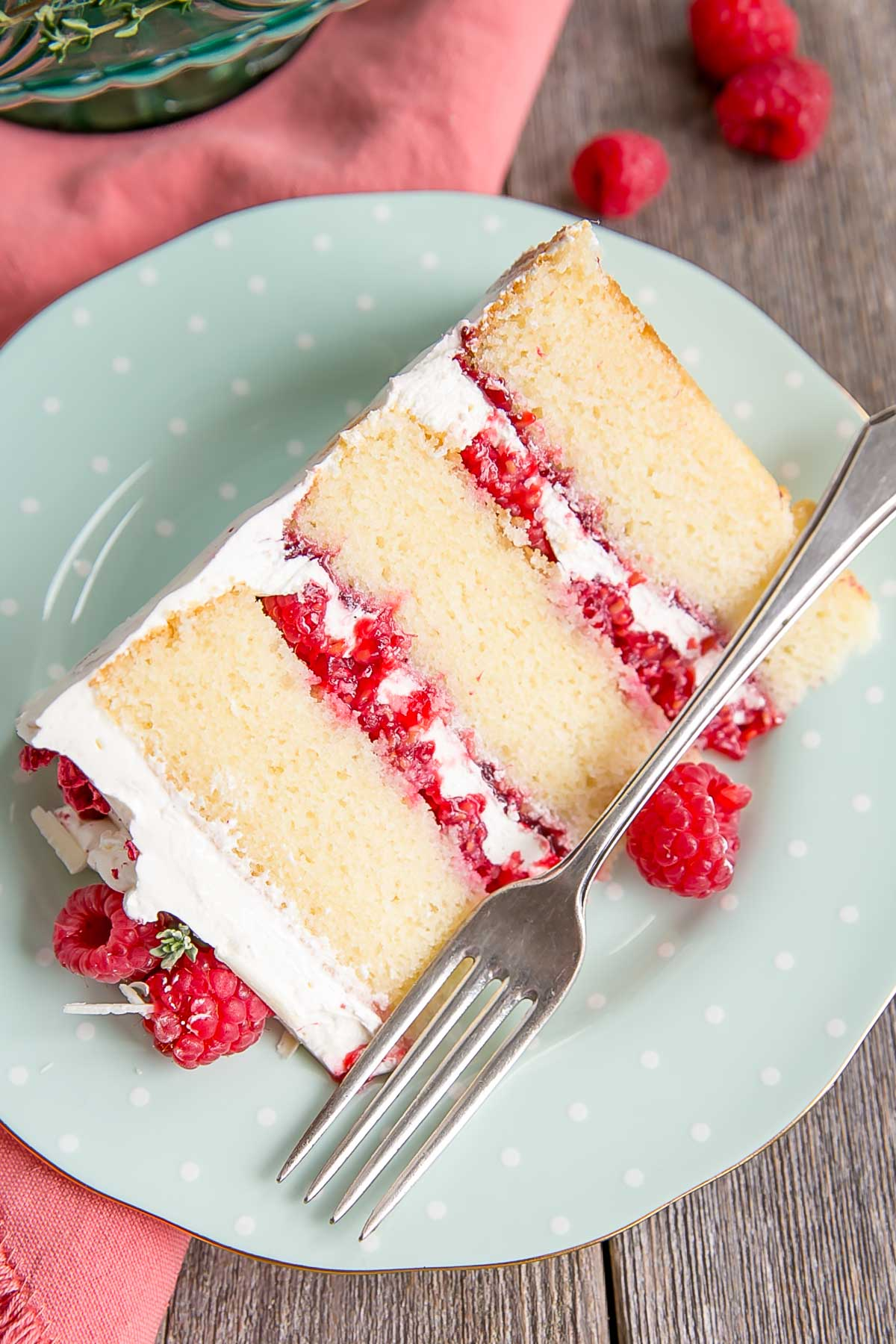 Slice of white chocolate cake with fresh raspberries.