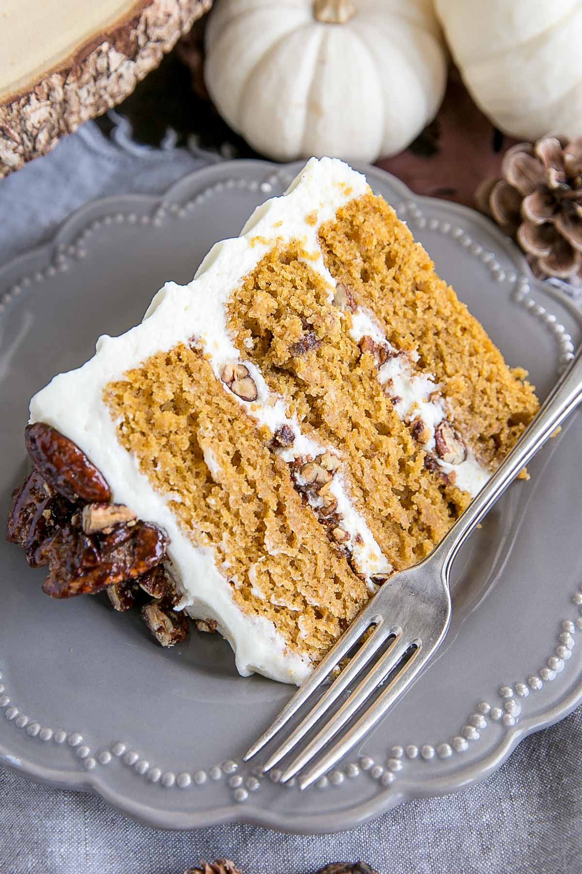 Slice of pumpkin cake -- three layers of cake with candied pecans and cream cheese frosting.