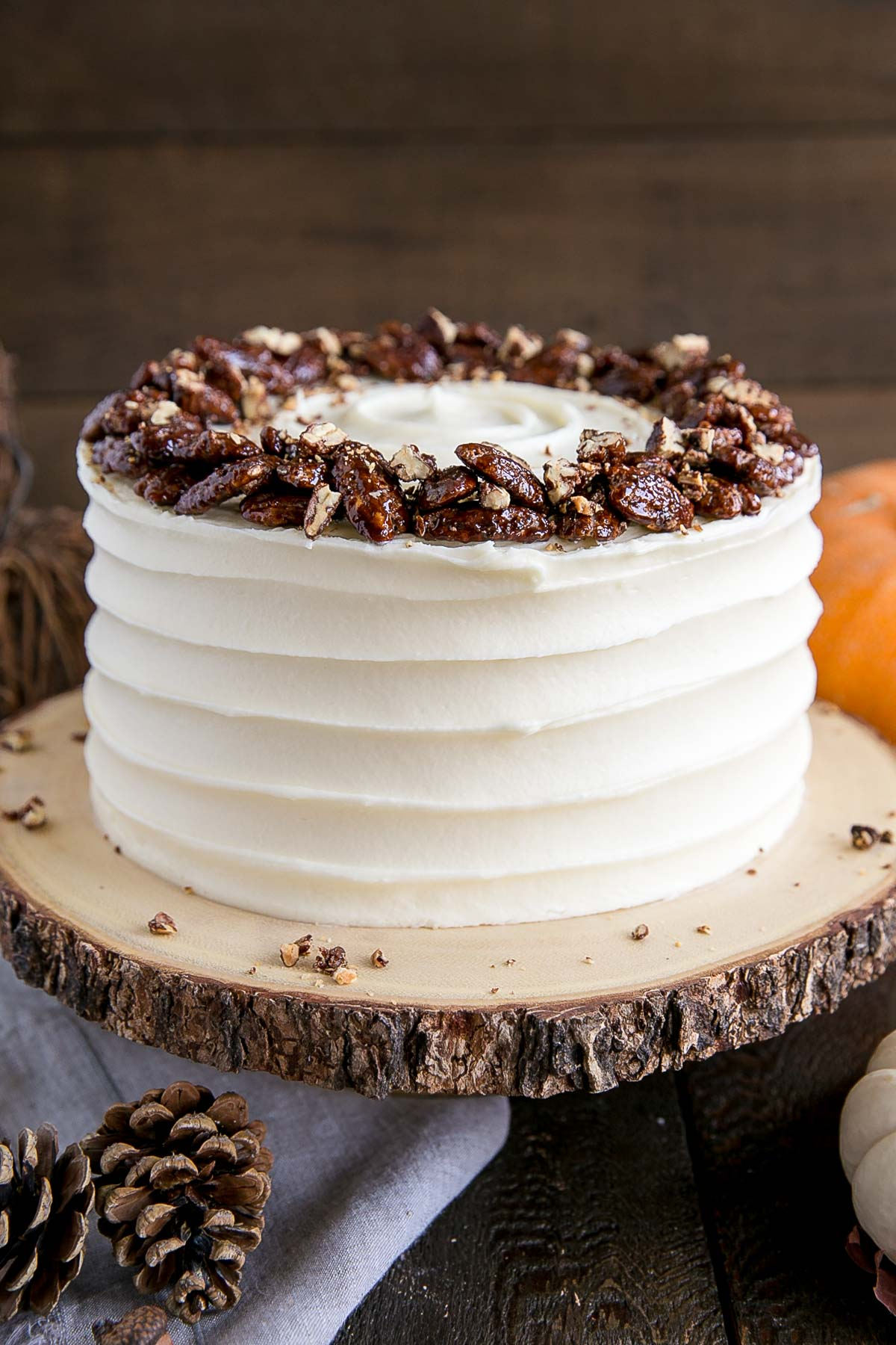 Glossy candied pecans on a pumpkin cake with cream cheese frosting.