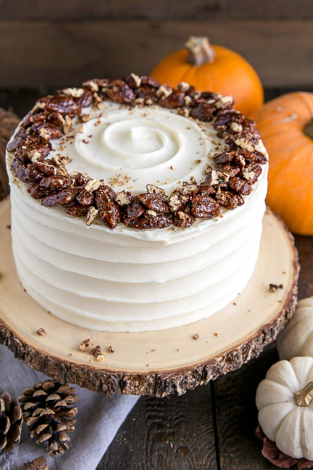 Pumpkin cake with cream cheese frosting on a rustic cake stand.