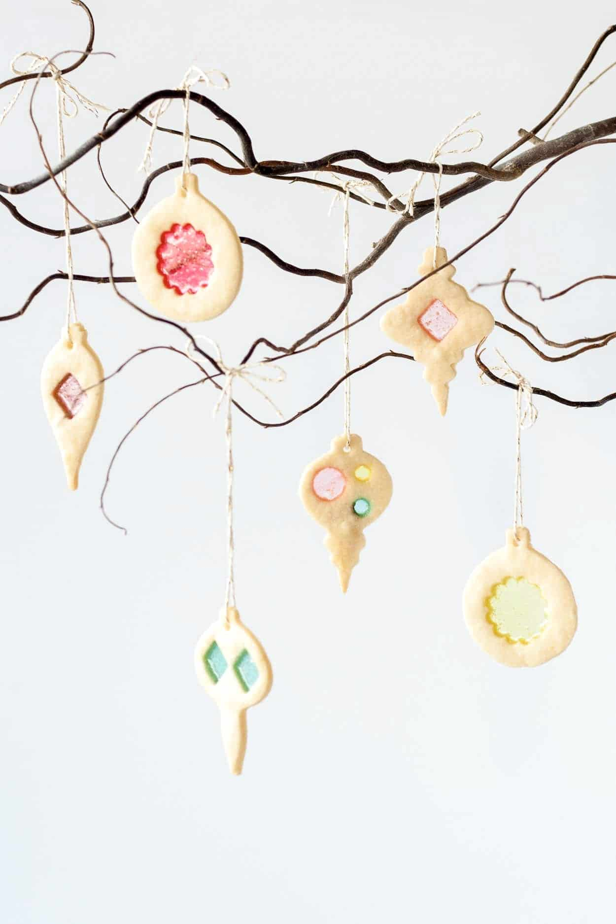 Stained glass cookie ornaments hanging from a tree branch.