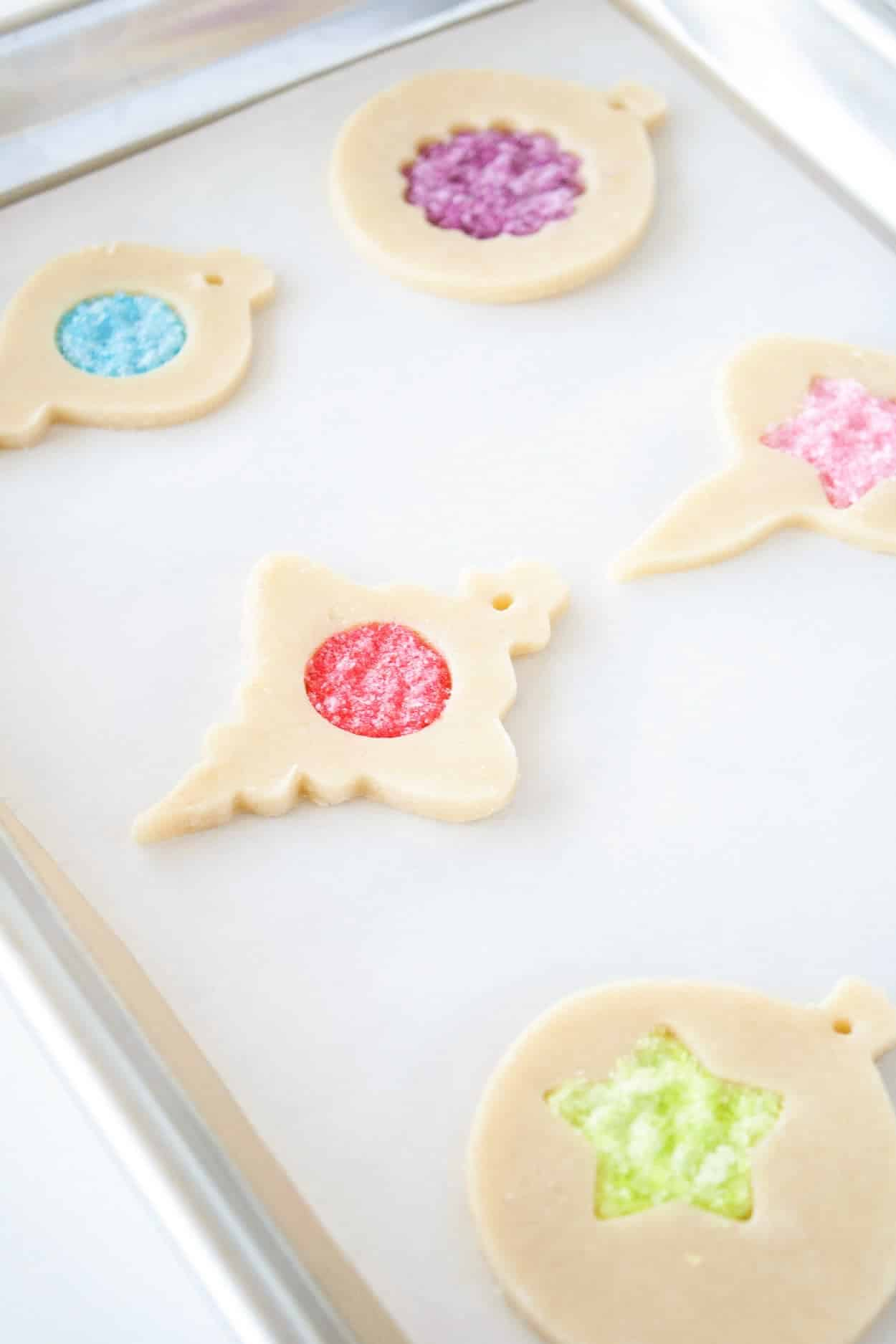 Unbaked stained glass cookies on a cookie sheet