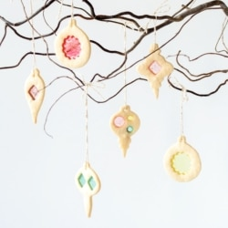 Stained glass cookies hanging from a tree branch.