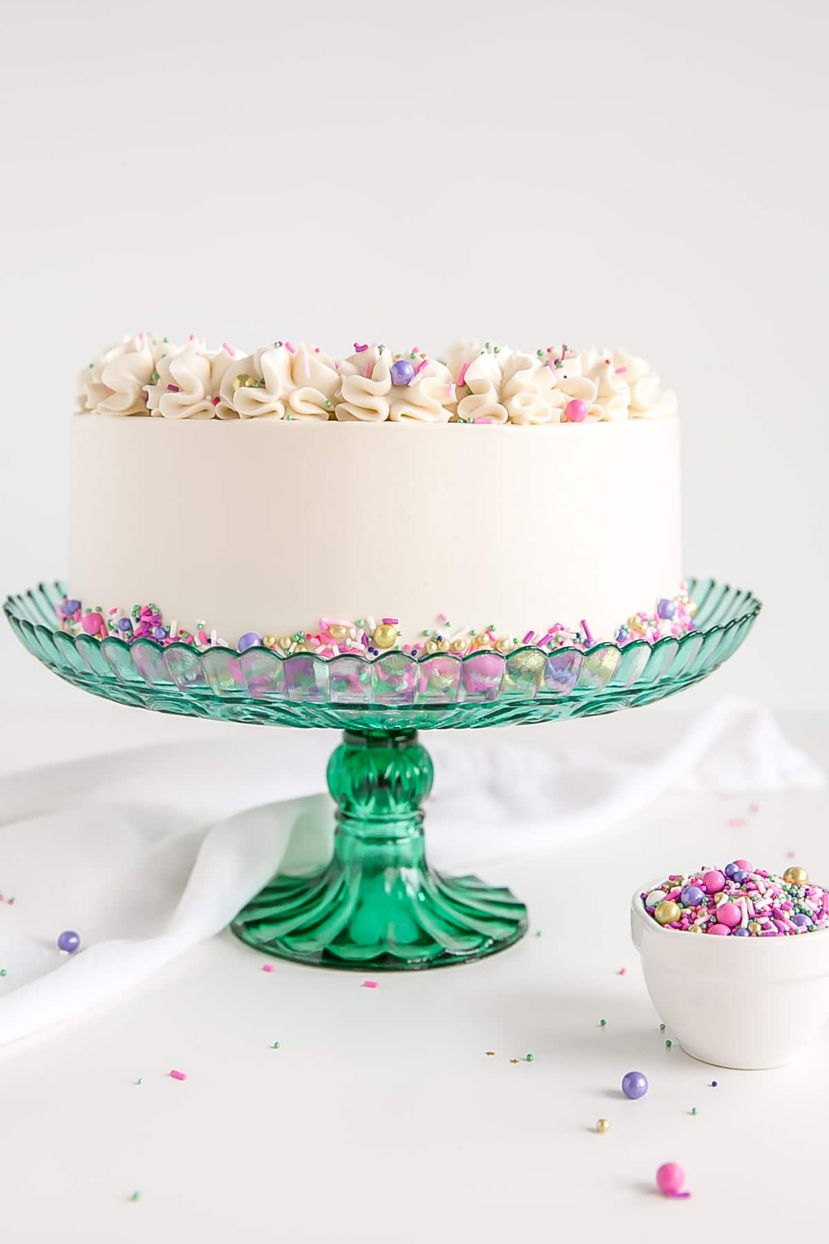 Profile shot of white cake with white buttercream and sprinkles.