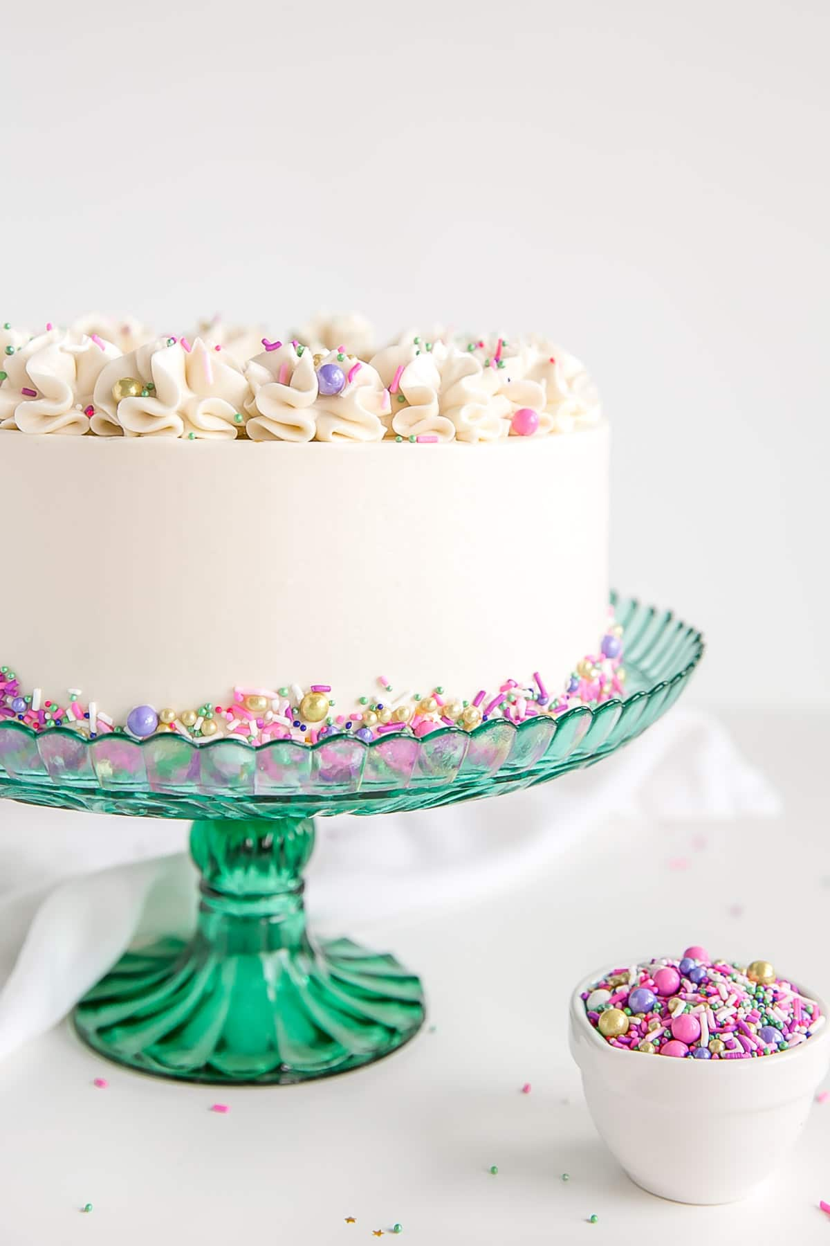 Side shot of a white cake on a green cake stand.