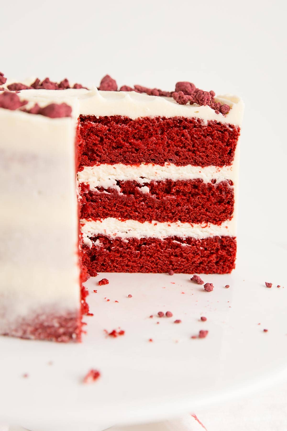 Cross-section of a three layer red velvet cake with cream cheese frosting.