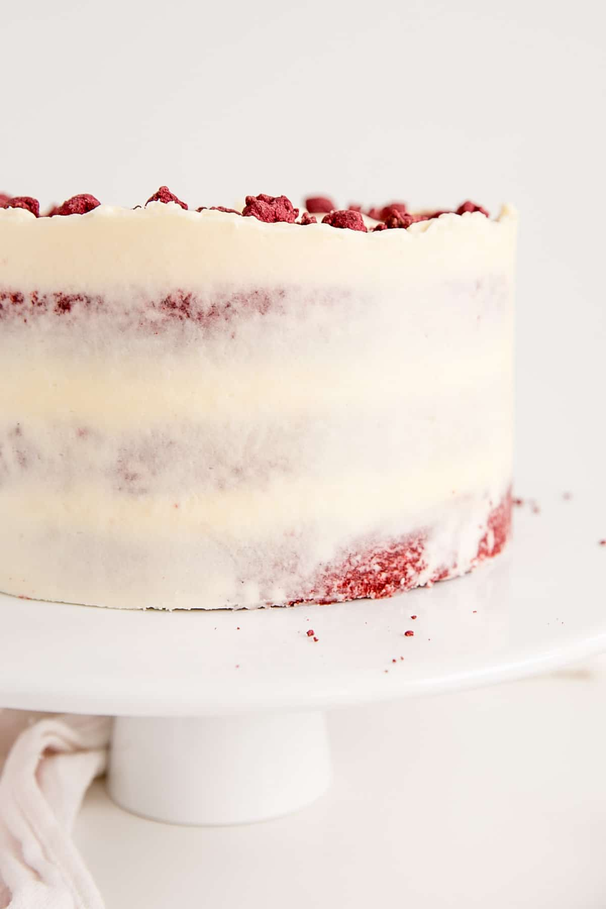 Close up side picture of a naked red velvet cake.