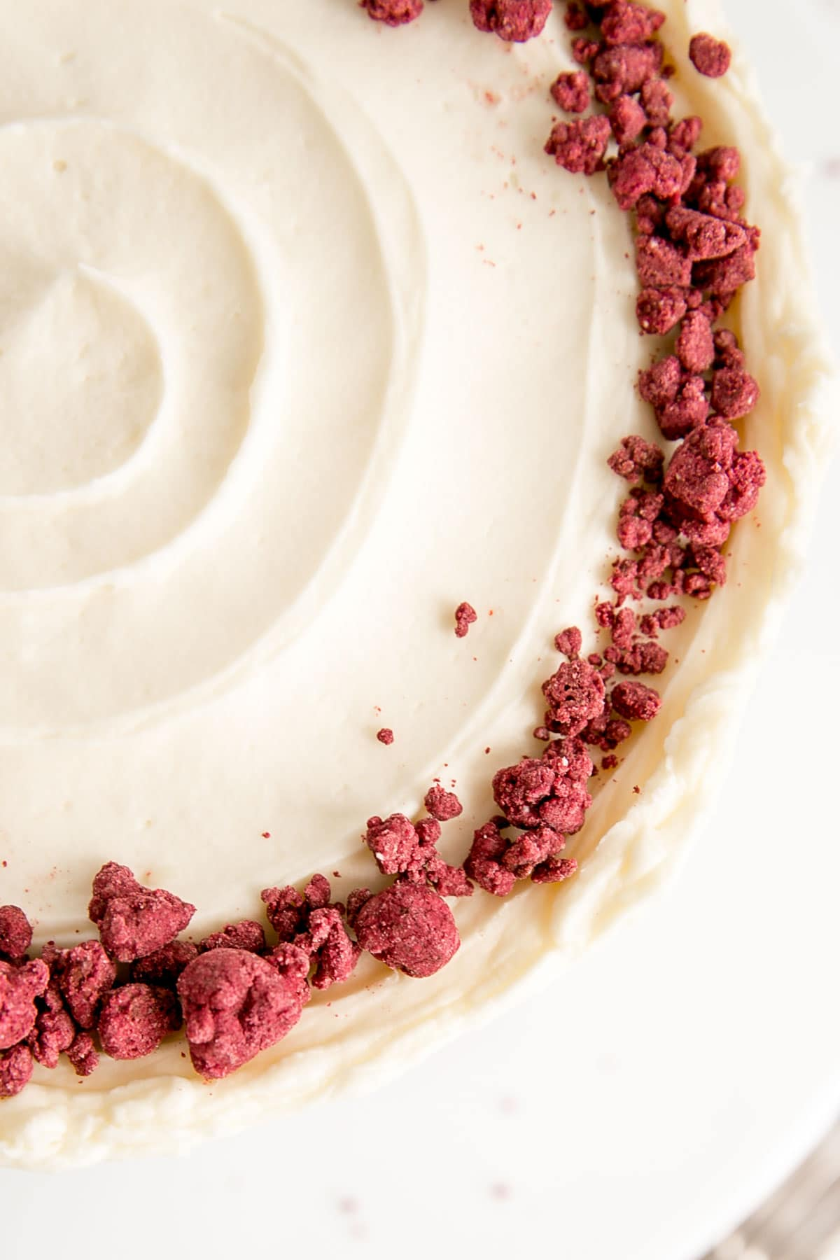 Overhead picture of crumble on top of a red velvet cake with cream cheese frosting.
