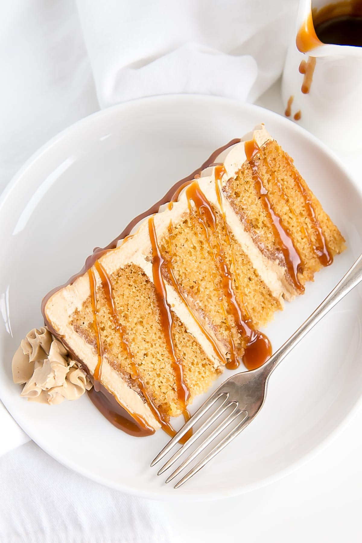 Slice of caramel cake on a plate, drizzled with more caramel.