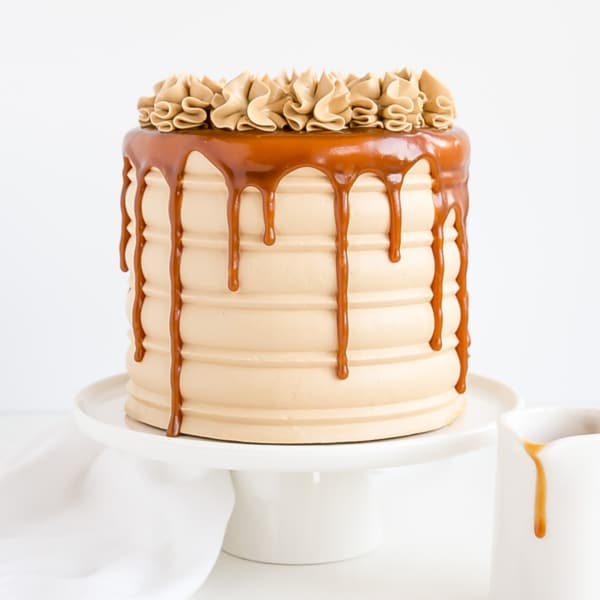This Caramel Cake is perfect for that die hard caramel fan in your life. Homemade caramel sauce is used in the cake layers, frosting, and the drip! | livforcake.com