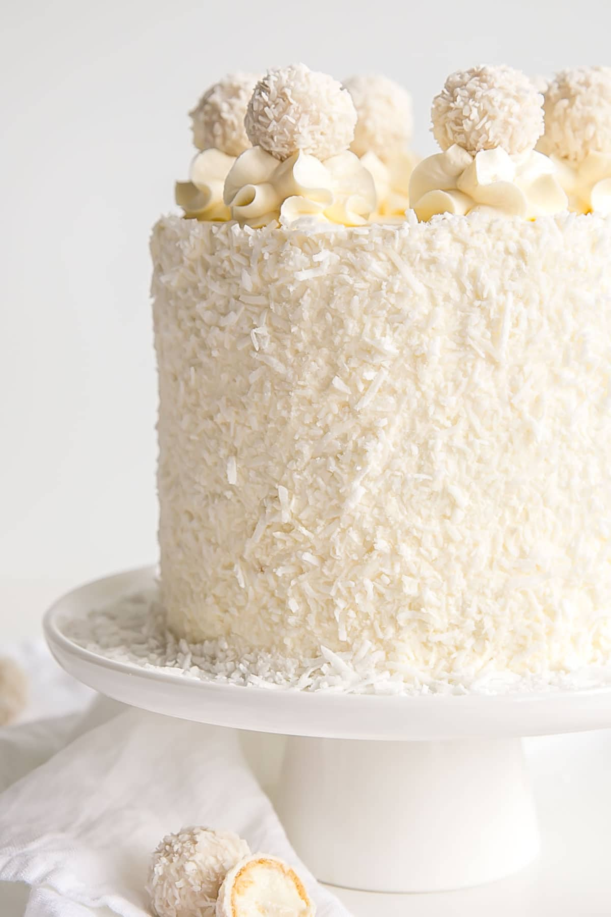 Close up of a coconut almond cake with Raffaello's on top.