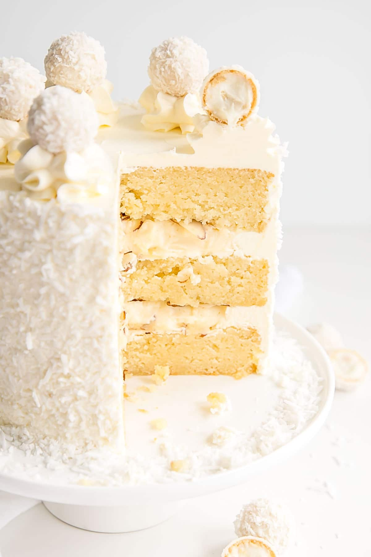 Cross section of a Raffaello Cake with almond cake layers and coconut cream custard.