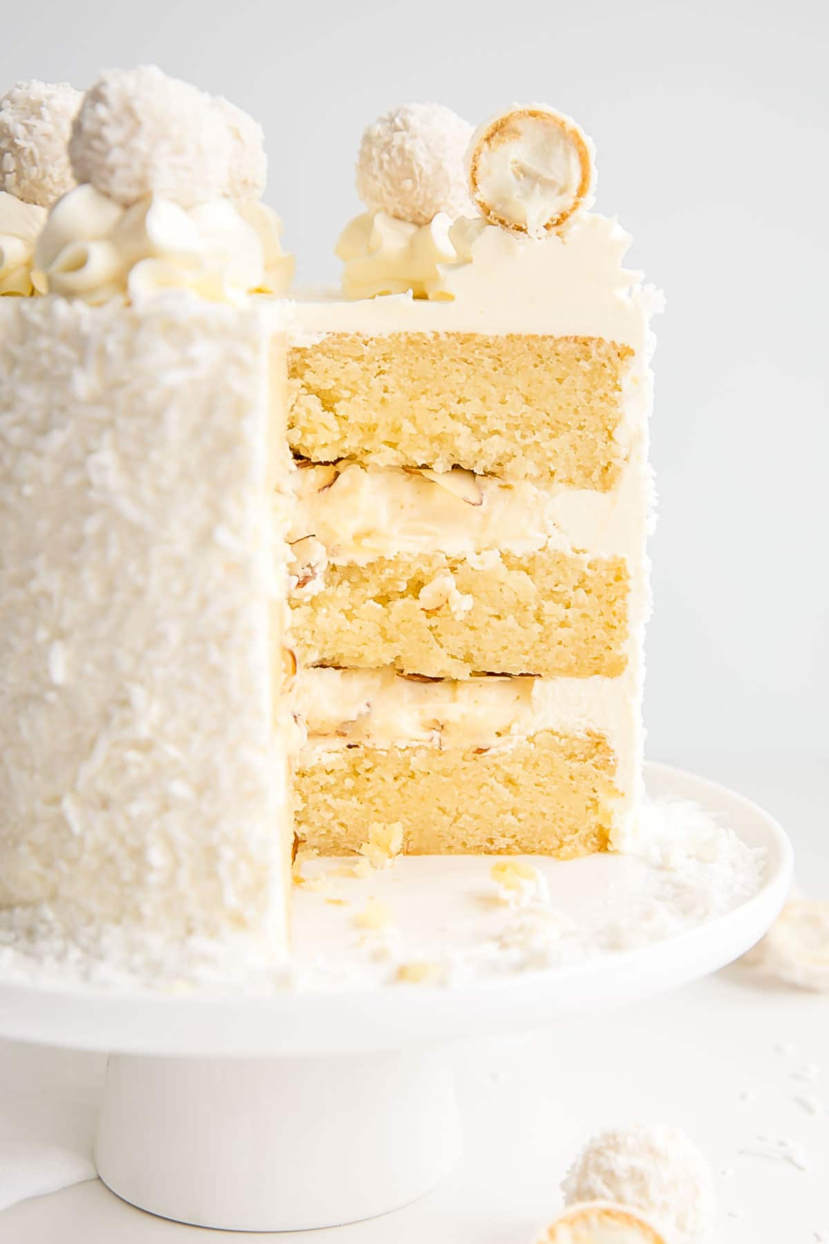 This Raffaello Cake is a coconut lover's dream! Layers of moist and tender almond cake, coconut custard, and coconut Swiss meringue buttercream! | livforcake.com