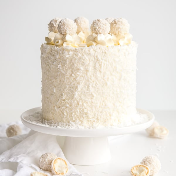 This Raffaello Cake is a coconut lovers dream! Layers of moist and tender almond cake, coconut custard, and coconut Swiss meringue buttercream. | livforcake.com