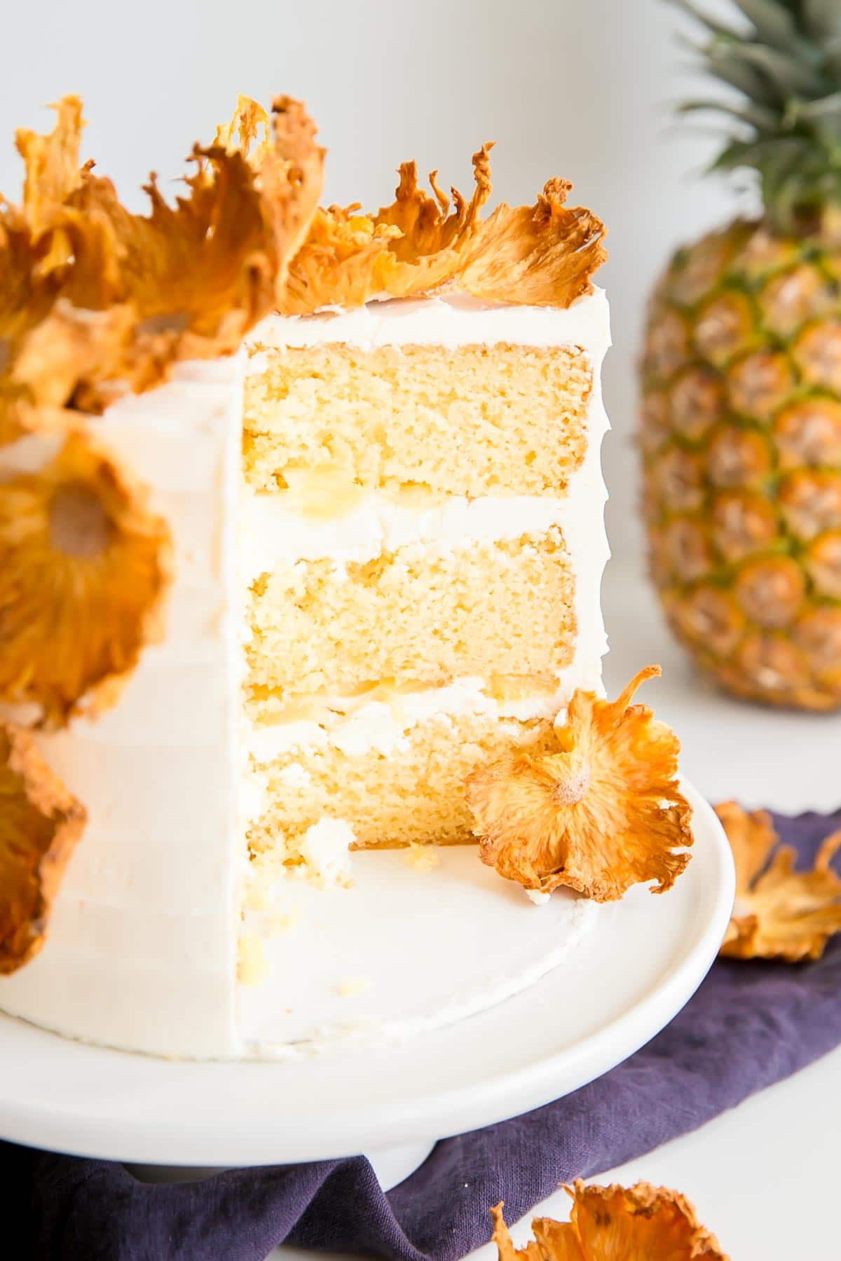 Cross-section image of a pineapple cake showing the cake layers, frosting, and fresh pineapple.