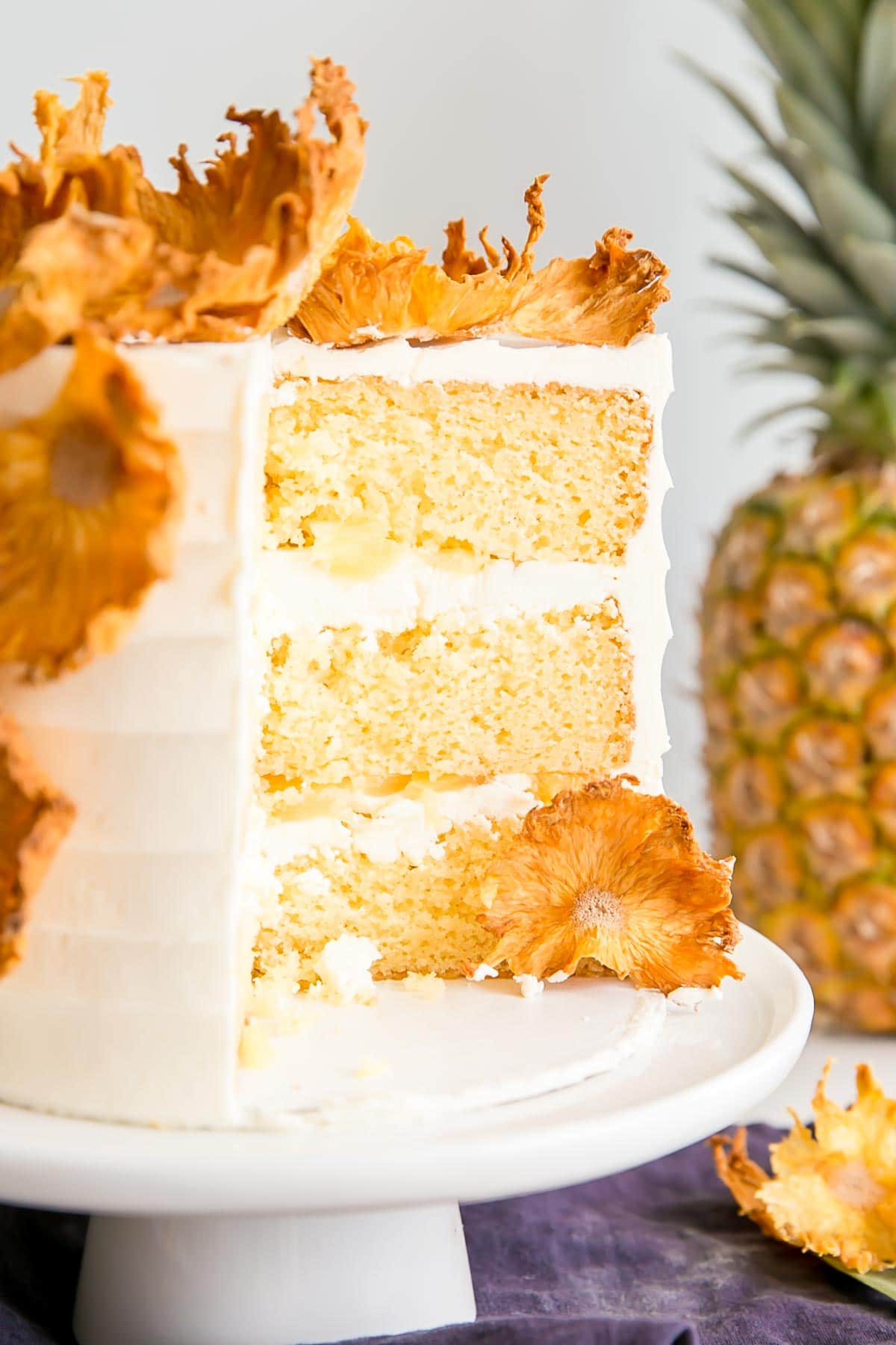 Pineapple cake with some slices cut out showing the cake layers.