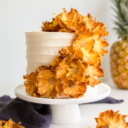 This Pineapple Cake is the perfect tropical dessert for summer! Dried pineapple flowers adorn this pineapple infused cake with fresh pineapple and pineapple buttercream. | livforcake.com