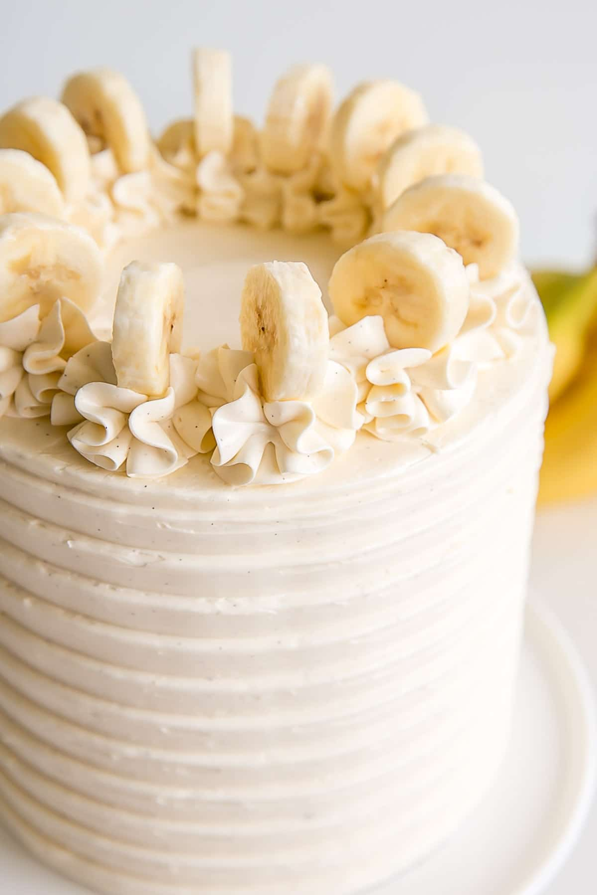 Close up of the top of the cake with rosettes and fresh banana slices.