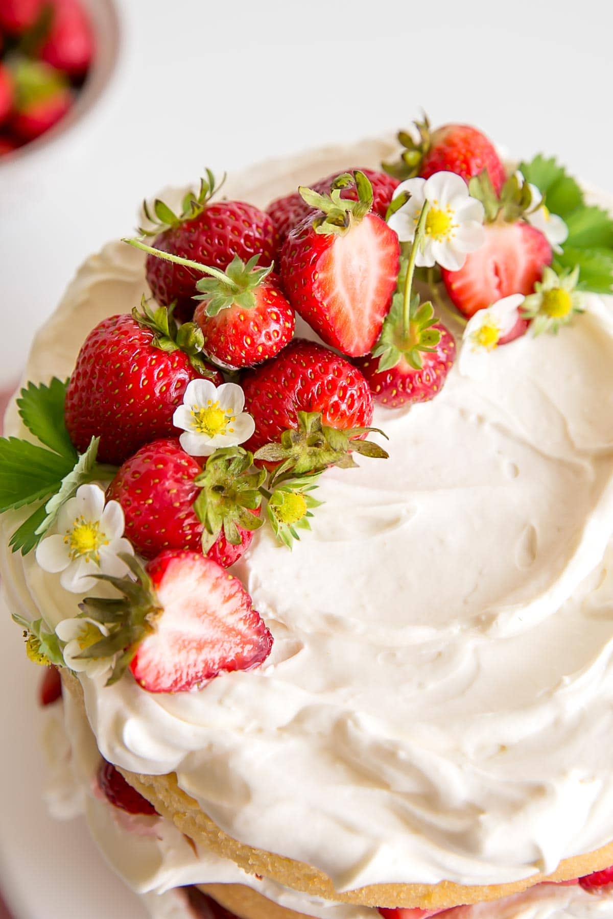 Fresh strawberries and strawberry flowers on top of mascarpone cream on the cake