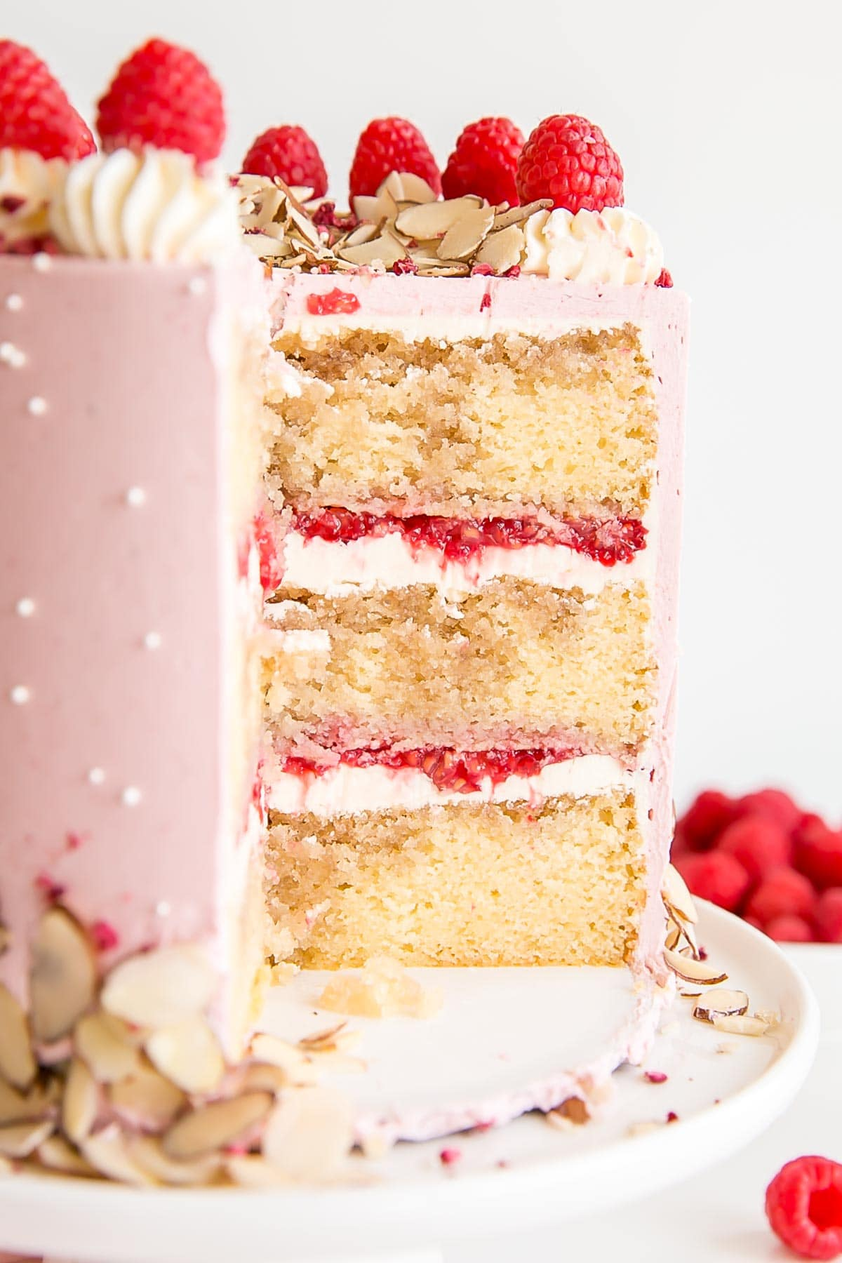 Cross-section of cake showing almond cake layers, almond buttercream, and fresh raspberries.