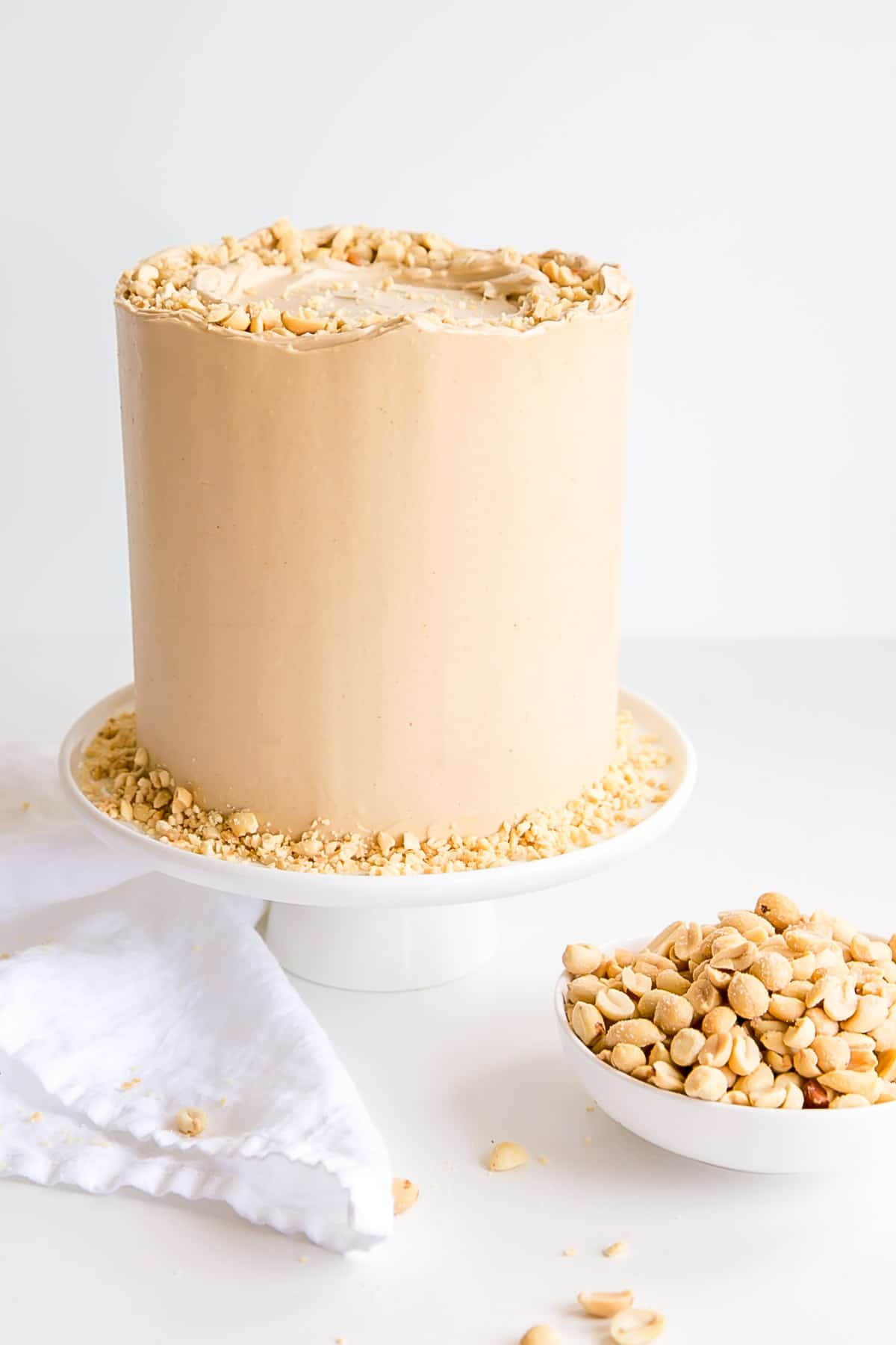 Cake on a white cake stand with a bowl of peanuts next to it.