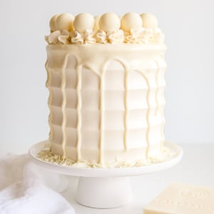 This White Chocolate Cake is both decadent and delicious! White chocolate is incorporated into the cake layers, the frosting, and the drip for a stunning monochrome effect.