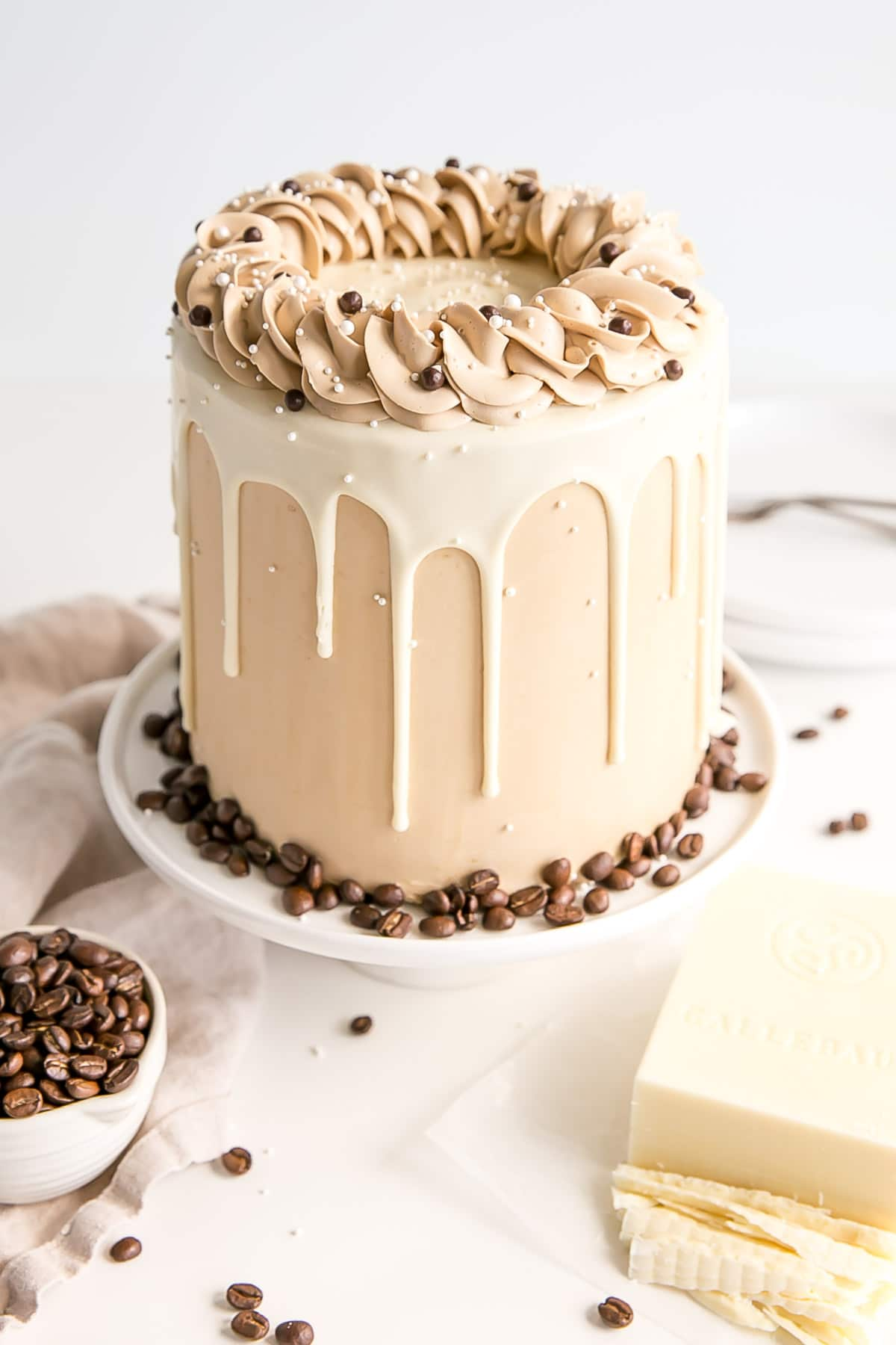 Angled shot of the cake with chopped white chocolate and coffee beans in the foreground.