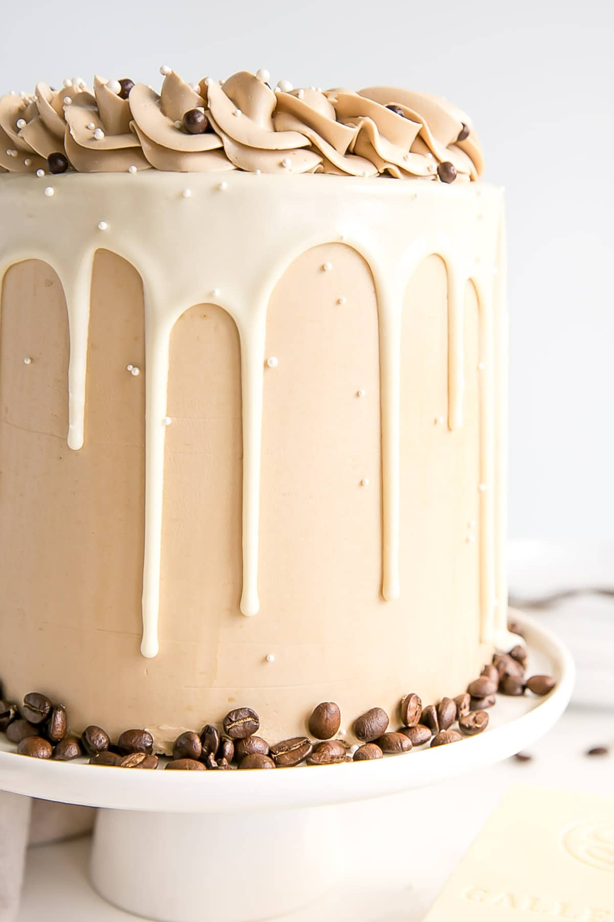 Close up of the side of the cake showing the frosting and the white chocolate ganache drip.