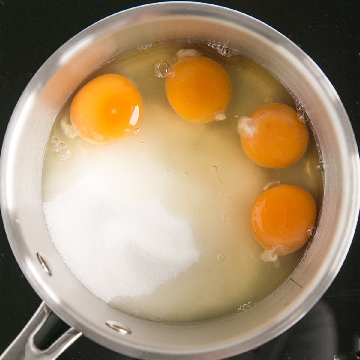 Eggs and sugar in a pot.