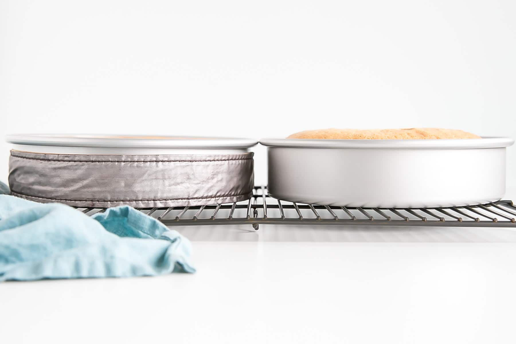 Tow cake pans side by side, one with an evenbake strip on it.