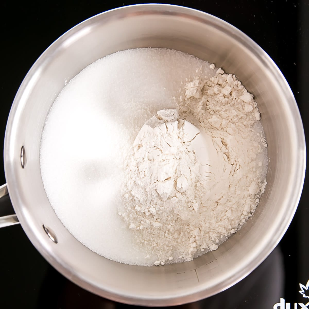 Flour, sugar, and salt in a pot.