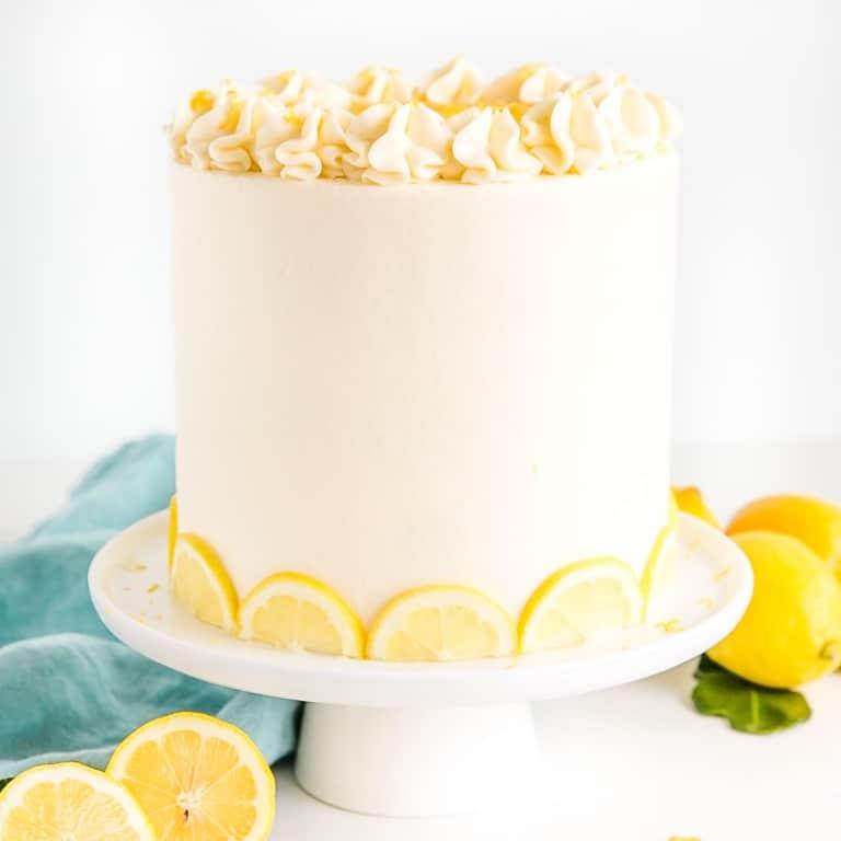 Lemon cake on a white cake stand.