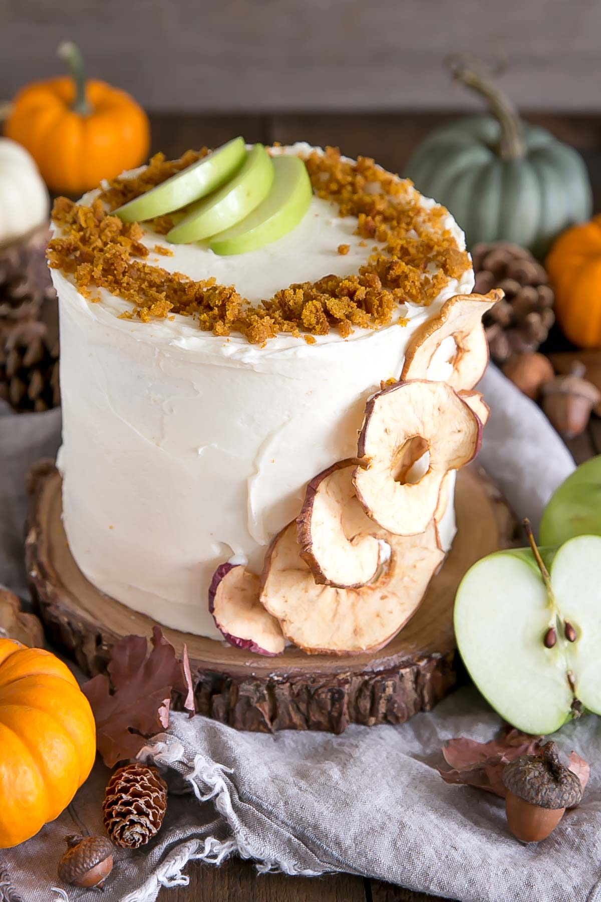 Pumpkin cake on a rustic wood cake stand with Fall decor around it.