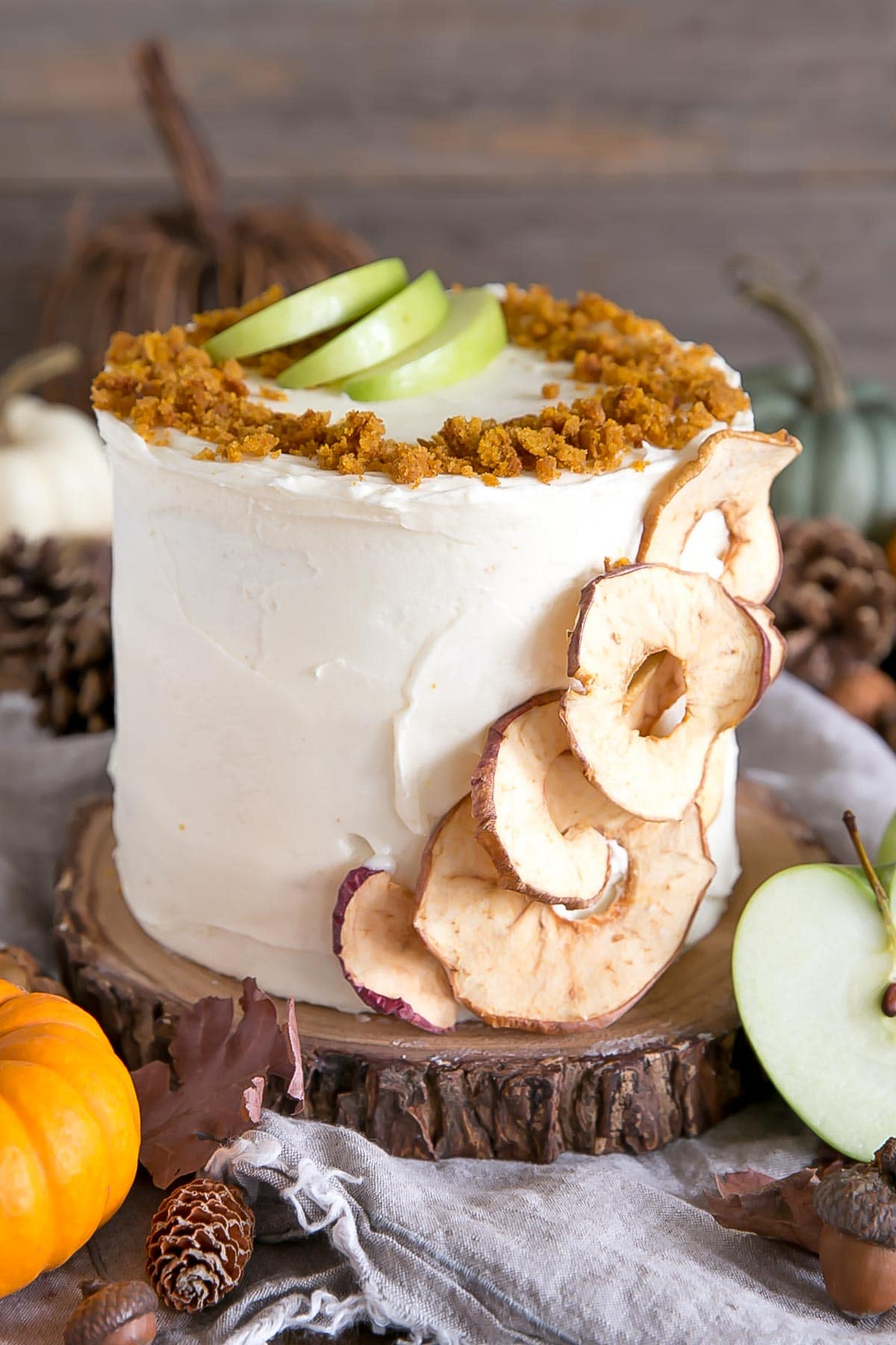 Pumpkin cake with apple pie filling frosted in a cream cheese frosting. Decorated with dried apple slices and pumpkin cake crumbs.