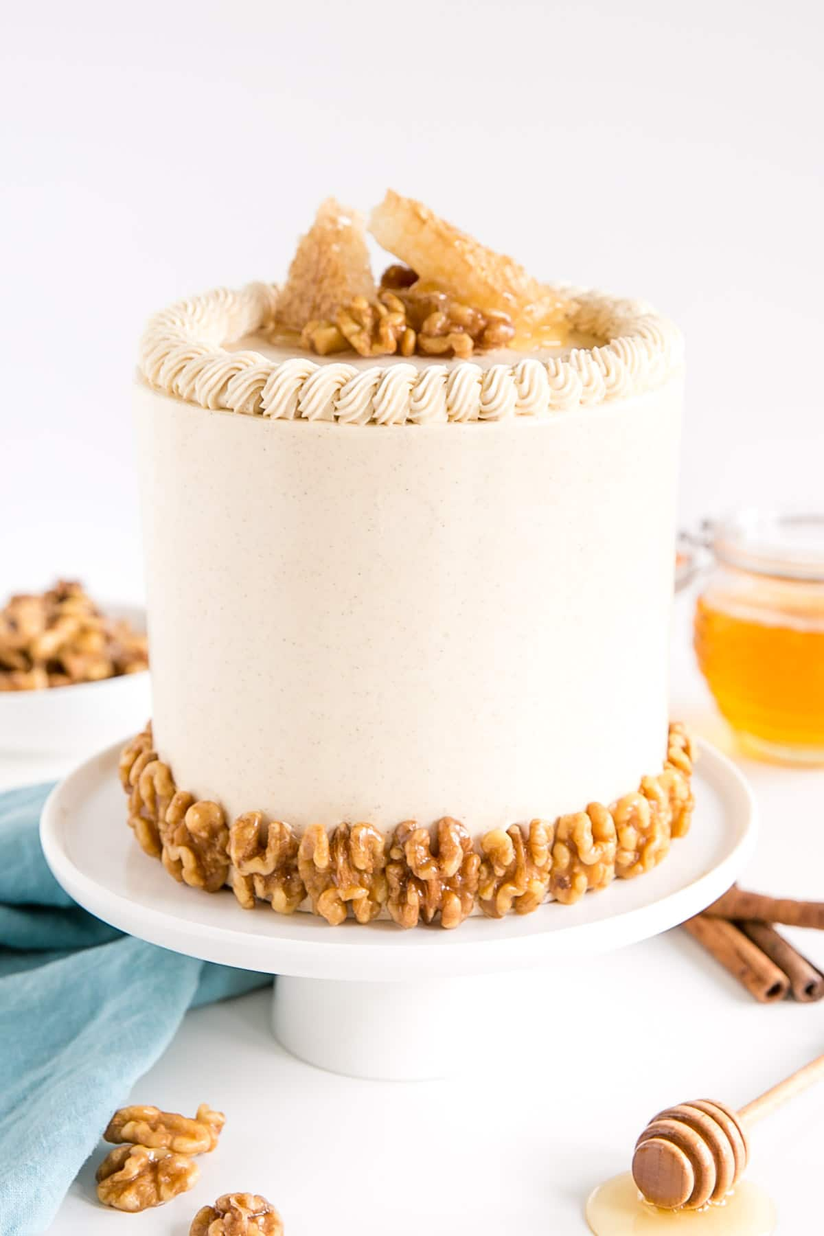 Cake on a white cake stand. Honey walnuts along the bottom and honeycomb on the top.
