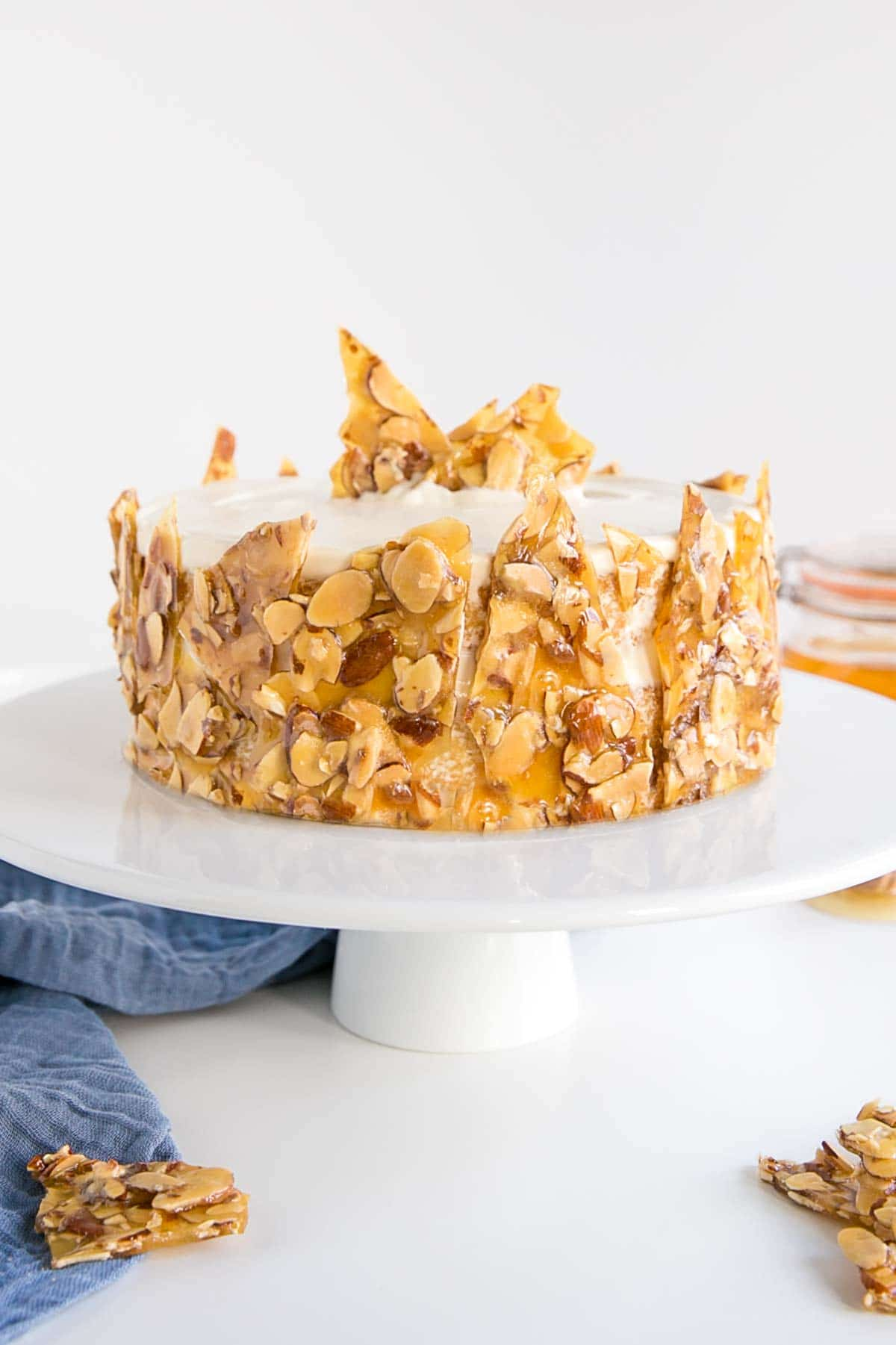 Honey Almond cake on a white cake stand with a blue cloth under it.