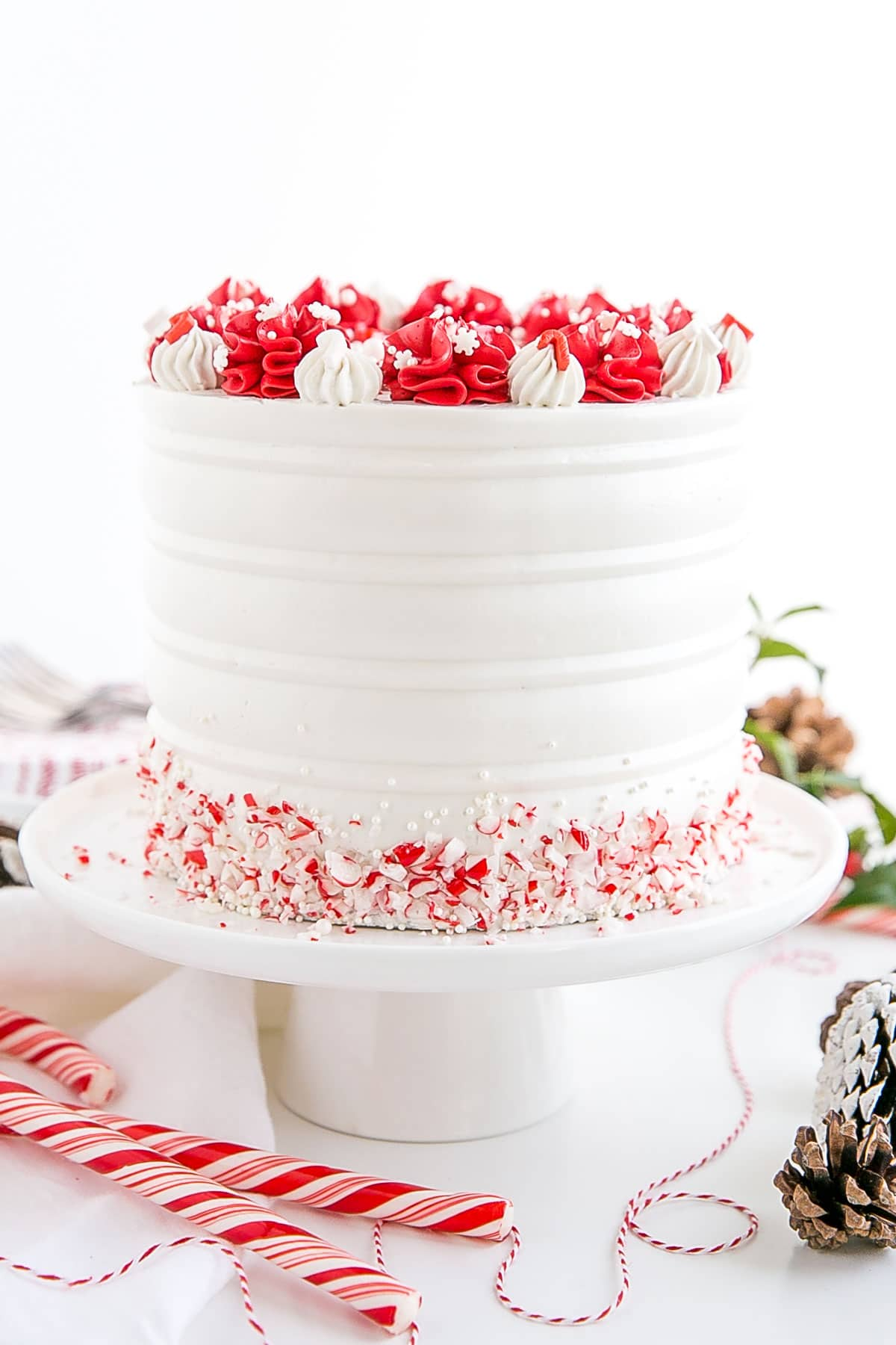 Red and white cake on a white cake stand.