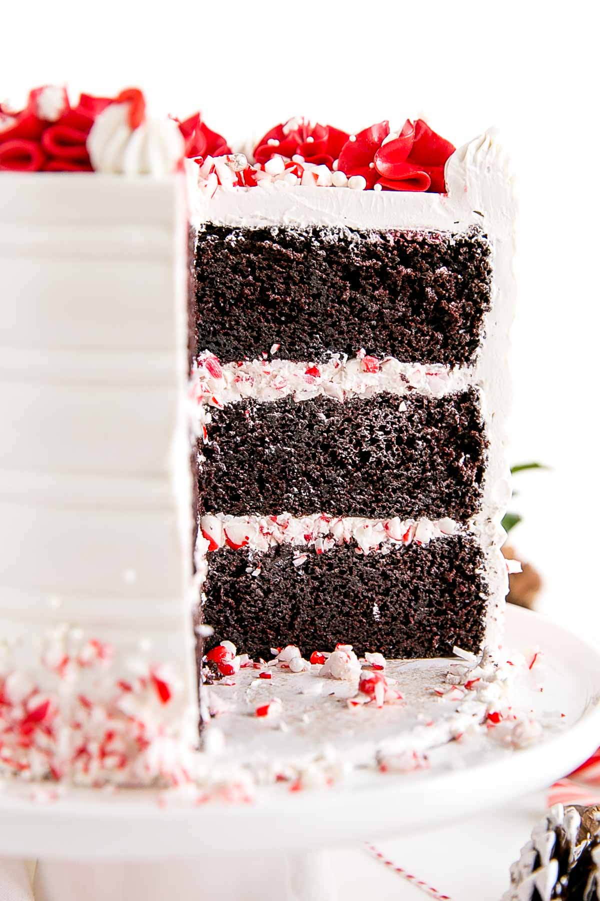 Cross-section showing the chocolate cake layers and crushed candy canes and frosting between them.
